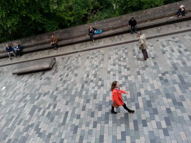 Brighton. Woman walking, people sitting on the street